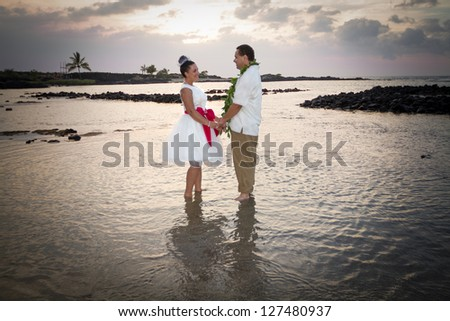 Newlywed couple standing in the warm, shallow waters of Hawaii. Horizontal portrait. - stock photo