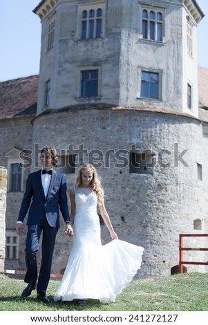 Newlywed couple taking a walk near by a fortress, sharing happiness together. - stock photo
