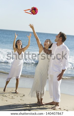 Newlywed couple with happy bride throwing her bouquet towards the bridesmaid on beach - stock photo