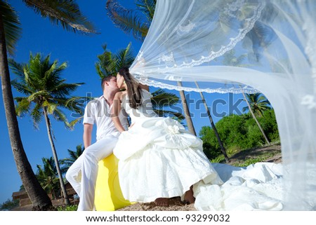 Newlyweds are sharing an intimate moment at an exotic location - stock photo