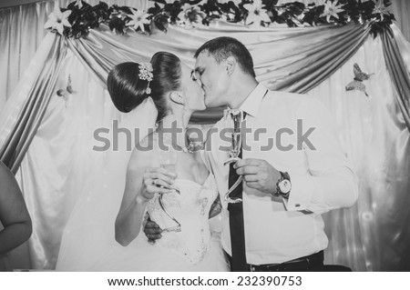 Newlyweds embraces. Beautiful newly married couple kissing at registry office. - stock photo