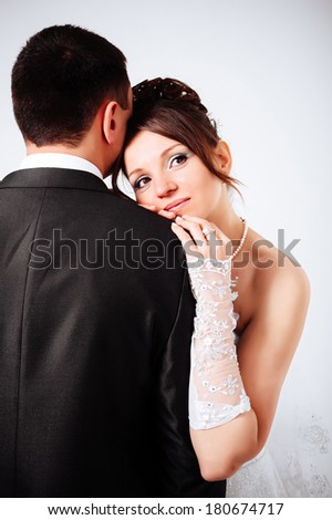 newlyweds embracing and kissing. Cute young married couple posing on white background. Bridal happy couple isolated on white background. Bouquet of flowers, wedding dress - stock photo