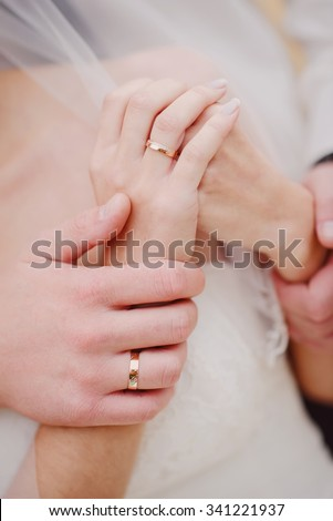 newlyweds holding each other's arms tight - stock photo