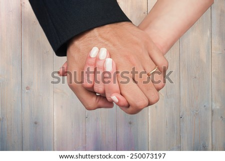 Newlyweds holding hands close up against pale grey wooden planks - stock photo