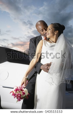 Newlyweds hugging by limo - stock photo