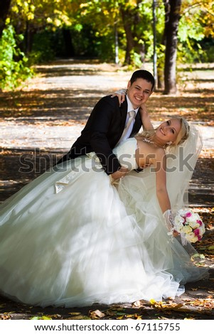 Newlyweds in autumn park, the groom holds the bride leaning for support. - stock photo