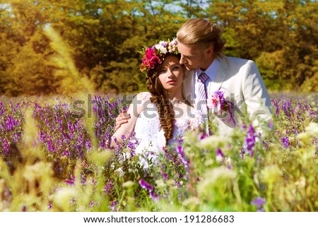 newlyweds in the summer outdoors in a grass - stock photo