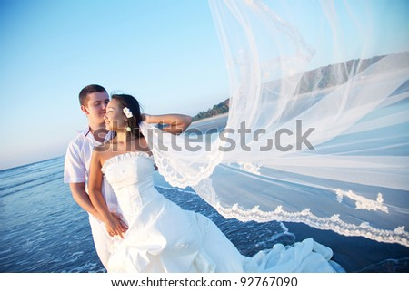 Newlyweds on the beach at sunset - stock photo