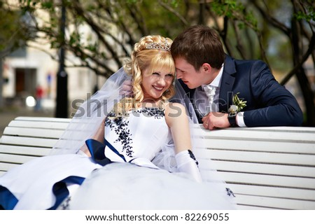 Newlyweds on the bench in park - stock photo