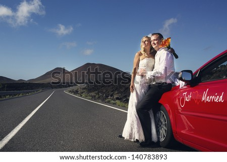 "Newlyweds on the road next to the red car with inscription ""Just Married"". Canary Islands. - stock photo"