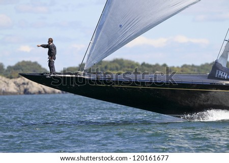 NEWPORT, RI - SEPTEMBER 11:  Unidentified foredeck crewman on bow of J Class Hanuman during start of Newport Bucket Regatta in Newport, RI on September 11, 2010. - stock photo