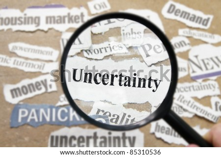 News headlines and magnifying glass with Uncertainty text - stock photo