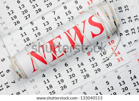 news.  Roll of newspapers tied with a rope lying on the calendar - stock photo