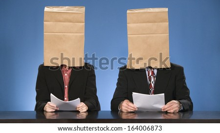Newscasters sitting doing the news with paper bags over their heads. - stock photo