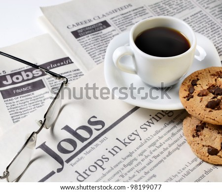 Newspaper classifieds and coffee cup with cookies - stock photo