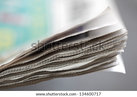 Newspaper concept edge of newspaper pages with shallow depth of field - stock photo