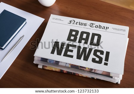 "Newspaper concept with hot topic ""Bad news"" lying on office desk. - stock photo"