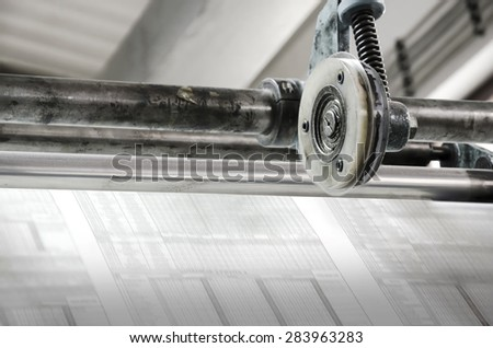 Newspaper offset printing machine roll of paper close up - stock photo