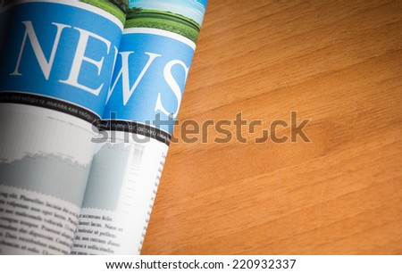 Newspaper on the table with very shallow depth of field and copy space. -Custom Design newspaper. - stock photo
