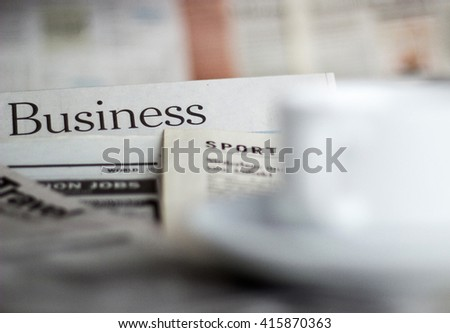 Newspapers and coffee cup macro shot with shallow depth of field - stock photo