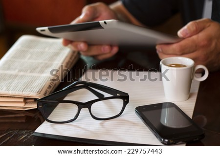 Newspapers and coffee cup, reading glasses, striped paper, hands holding tablet, cell phone. - stock photo