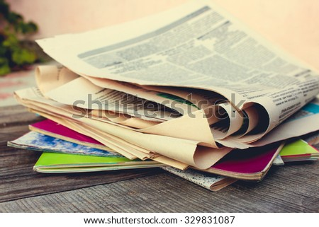 Newspapers and magazines on old wood background. Toned image.   - stock photo