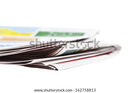 Newspapers are stacked high on a white background - stock photo