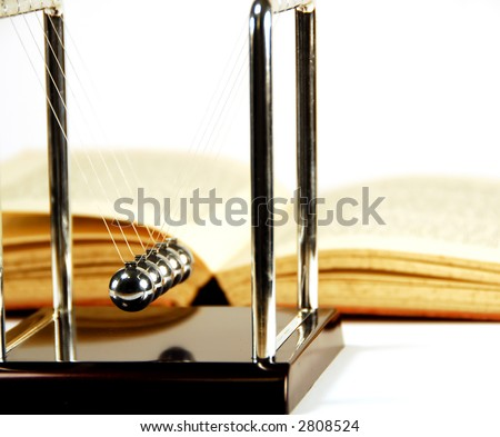 newton balls and a book on white background - stock photo