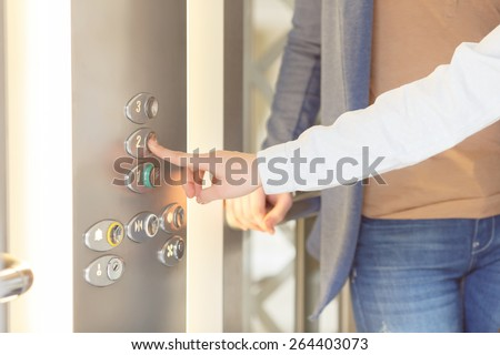 Next floor. Close up of the female hand pushing the button inside the elevator - stock photo