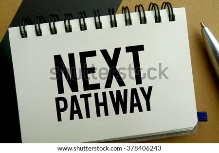 Next pathway memo written on a notebook with pen - stock photo
