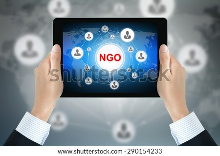 NGO (or Non-Governmental Organization) sign on tablet pc screen held by businessman hands - stock photo
