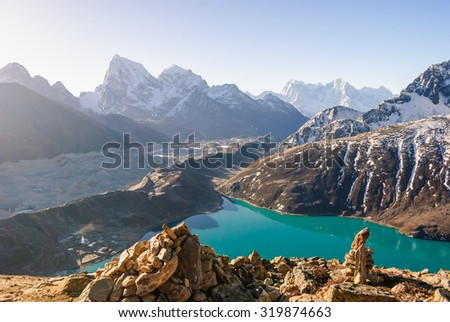 Ngozumpa Glacier flowing down from the high snow capped mountains of the Himalayas. View from Gokyo Ri, 5360 meters up in the Himalaya Mountains of Nepal - stock photo