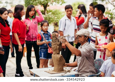 Nha Trang, VIETNAM - CIRCA February 2015 - unidentified vietnamese sculptor man with clay and figure on lunar new year festival - stock photo