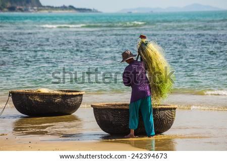 NHA TRANG, VIETNAM - NOV 28: Unidentified fishermen is working on the beach in Nha Trang, Vietnam. On Nov 28, 2014. - stock photo