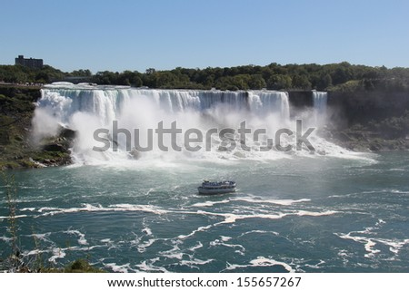 Niagara Falls American Falls. The American Falls portion of the world famous Niagara Falls, with a tourist vessel below. - stock photo