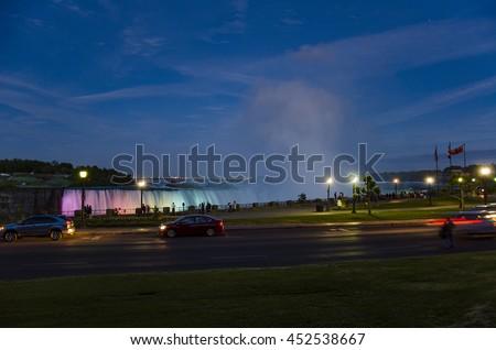 Niagara Falls City at night. Tourists and visitors admire the illuminated Canadian Falls in Ontario, Canada - stock photo