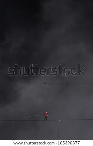 NIAGARA FALLS -JUNE 15: Nik Wallanda on a rope that is only 5 centimeters wide while crossing the Niagara Falls on a tightrope on June 15 2012 in Niagara Falls, Canada. - stock photo