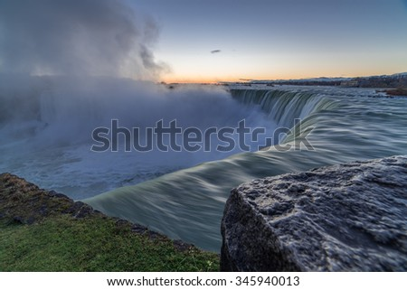 Niagara Falls on the Canadian side looking towards the horizon where the sun would be about to rise over horseshoe falls. - stock photo