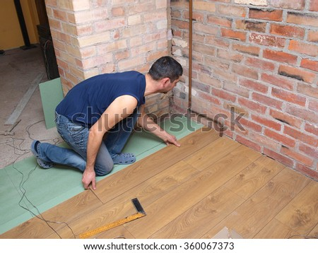 NICA, LATVIA - JANUARY 9, 2016: Construction worker is installing laminated floor in room. - stock photo