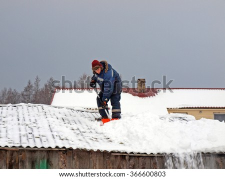 NICA, LATVIA - JANUARY 24, 2016: Young man with shovel is working on barn roof remove the snow. - stock photo
