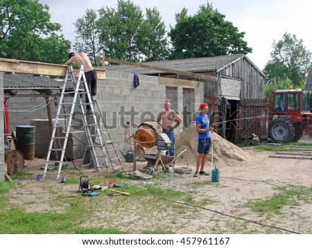 NICA, LATVIA - JULY 24, 2016: Construction workers are building small country farm garage wall from concrete blocks.                                - stock photo