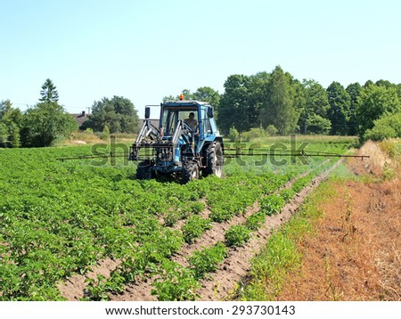 NICA, LATVIA - JULY 4, 2015: Country farmer spray the potato field with tractor powered sprayer against Colorado potato beetles front view. - stock photo