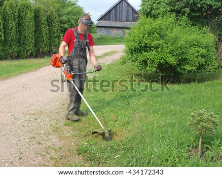 NICA, LATVIA - JUNE 8, 2016: Young man is cutting grass with string mower. - stock photo