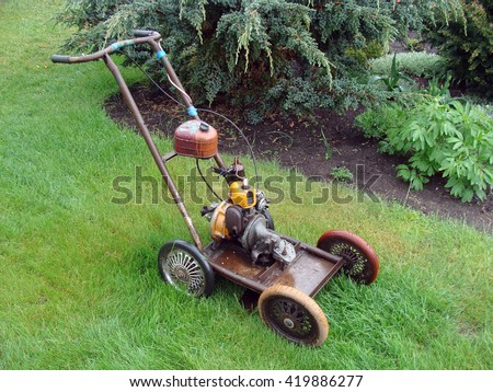 NICA, LATVIA - MAY 13, 2016: Homemade lawn mower is made from russian chain saw engine and baby carriages wheels. - stock photo