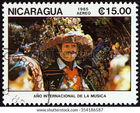 """NICARAGUA - CIRCA 1985: A stamp printed in Nicaragua from the """"International Music Year """" issue shows masked dancer in brimmed hat, circa 1985.  - stock photo"""