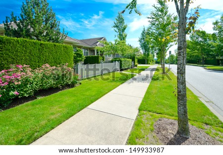 Nice and clean sidewalk at the empty street and trimmed green and wooden fence aside. Neighborhood scenery, landscape design. - stock photo