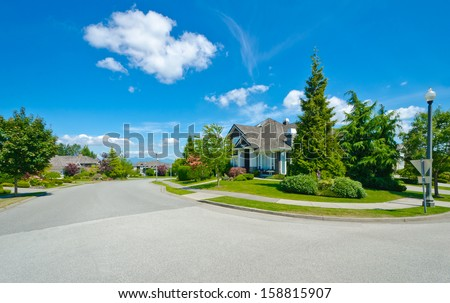 Nice and comfortable neigborhood. Empty street with pedestrian sidewalk with row, line of the houses, homes in the suburbs of the North America. Canada. - stock photo