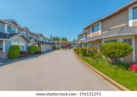 Nice and comfortable neighborhood. Some homes on the empty street in the suburb of North America. Canada. - stock photo