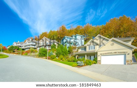 Nice and comfortable neighborhood. Some homes on the empty street in the suburbs of Vancouver. Canada. - stock photo