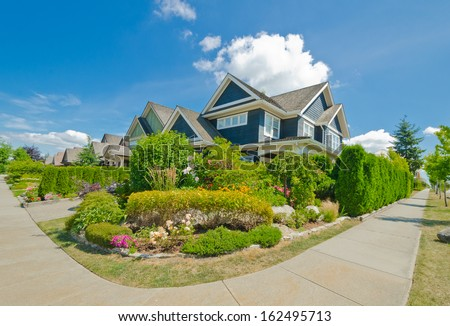 Nice and comfortable neighborhood. Some homes with nicely landscaped front yards in the suburbs of Vancouver, Canada. - stock photo